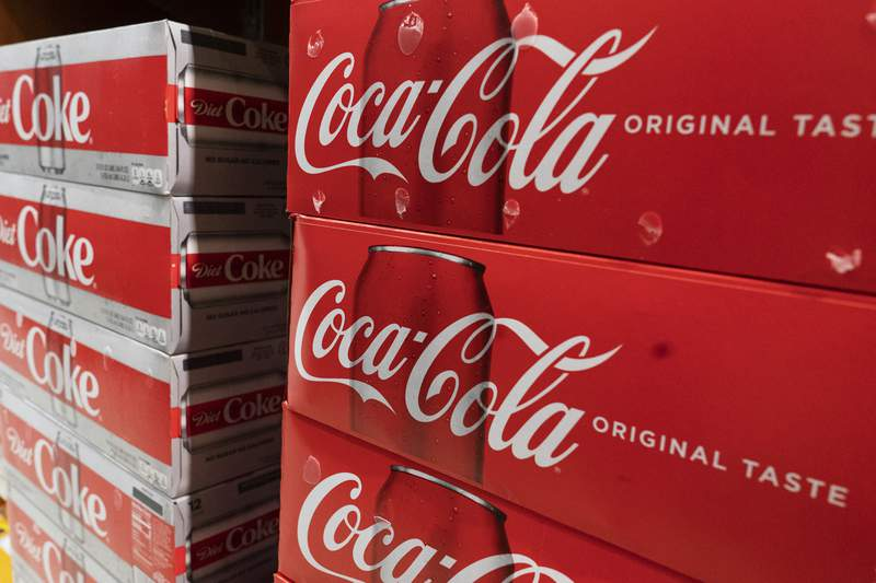 Cases of Coca-Cola are displayed in a supermarket, Monday, April 5, 2021 in New York.  Coca-Cola Co. saw higher-than-expected sales in the second quarter, Wednesday, July 21,  as the impact of the pandemic abated. The Atlanta-based soft drink giant said its revenue jumped 42% to $10.1 billion in the April-June period.  (AP Photo/Mark Lennihan)