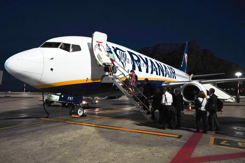 Passengers board a Ryanair airplane, in Palermo, Italy, Saturday, Sept. 15, 2018. Italys aviation authority, ENAC, has put RyanAir on notice that it has repeatedly violated rules aimed at curbing the spread of coronavirus, warning that the budget carrier risks suspension in Italy unless it complies. ENAC said in a statement Wednesday, Aug. 5, 2020 that RyanAir had repeatedly disregarded rules, calling it behavior disrespectful of the health measures in Italy.  They include requiring passengers to wear masks, restricting baggage on board to small items placed in plastic bags and preventing crowding at baggage pickup. (AP Photo/Andrew Medichini)