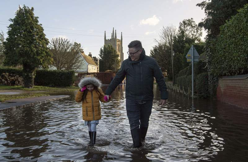 A man and girl walk through the flood water, in Great Barford, in Bedfordshire, England, Sunday, Dec. 27, 2020. Hurricane-force winds reaching up to 106 miles per hour (170 kph) and rainstorms battered parts of Britain, disrupting train services and stranding drivers in floodwaters. The Isle of Wight saw Storm Bellas strongest winds at 106mph, while parts of the south coast of England and north Wales also saw gusts of around 80mph (129 kph). (Joe Giddens/PA via AP)