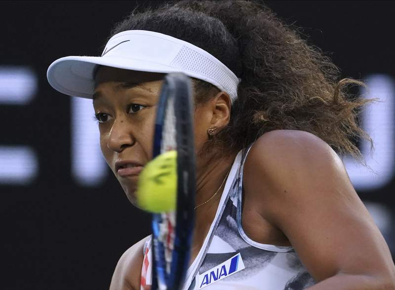 Japan's Naomi Osaka makes a backhand return to Coco Gauff of the U.S. during their third round singles match at the Australian Open tennis championship in Melbourne, Australia, Friday, Jan. 24, 2020. (AP Photo/Lee Jin-man)