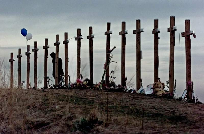 FILE - In this April 28, 1999, file photo, a woman stands among crosses posted on a hill above Columbine High School in Littleton, Colo., in remembrance of the people who died during a school shooting on April 20. (AP Photo/Eric Gay, File)