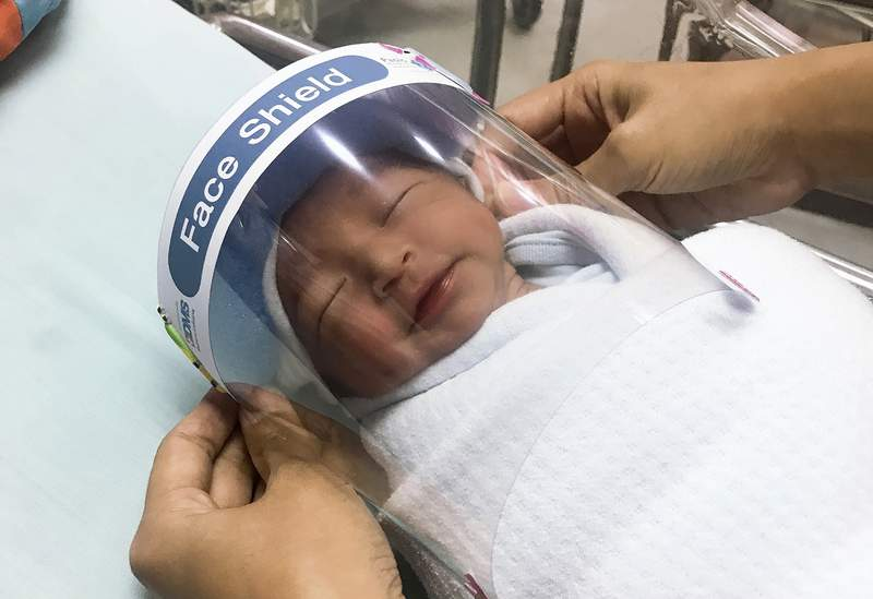 In this Friday, April 3, 2020, photo released by Paolo Hospital Samutprakarn, a nurse adjusts tiny face shield for a newborn baby to protect from new coronavirus at the newborn nursery of the hospital in Samutprakarn province, central Thailand. The new coronavirus causes mild or moderate symptoms for most people, but for some, especially older adults and people with existing health problems, it can cause more severe illness or death. (Paolo Hospital Samutprakarn via AP)