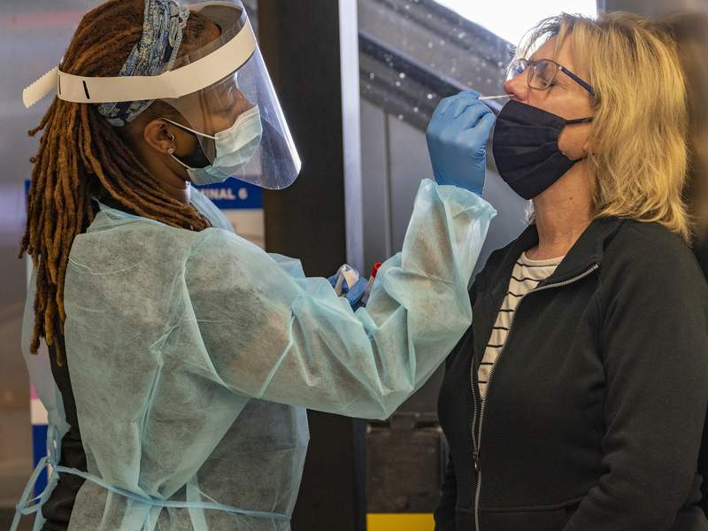 Traveler Patty Siegel, right, from Los Angeles gets a COVID-19 nasal swab test before a planned trip to Hawaii at the Los Angeles International Airport in Los Angeles Wednesday, Nov. 25, 2020. Residents were urged to avoid nonessential travel during what is typically the busiest travel period of the year. Anyone entering California was advised to quarantine for two weeks. (AP Photo/Damian Dovarganes)