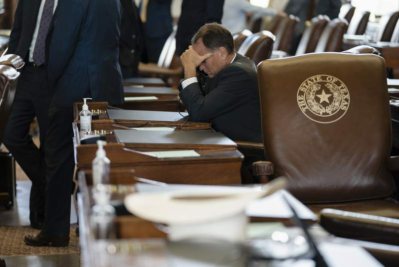 A legislator holds his head in his hand while sitting on the House floor on July 19, 2021.
