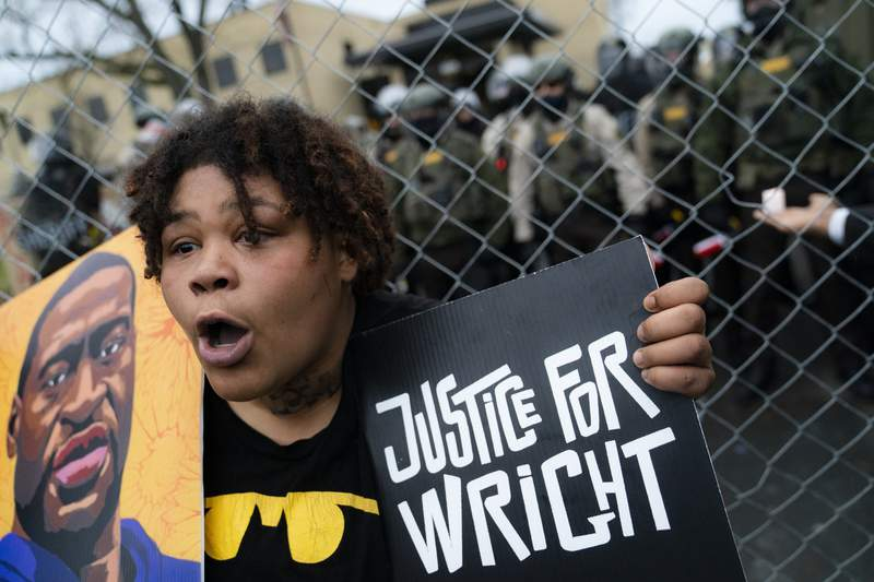A demonstrator reacts along a perimeter fence guarded by police during a protest decrying the shooting death of Daunte Wright, while also holding a rendering of George Floyd, outside the Brooklyn Center Police Department, Wednesday, April 14, 2021, in Brooklyn Center, Minn. (AP Photo/John Minchillo)