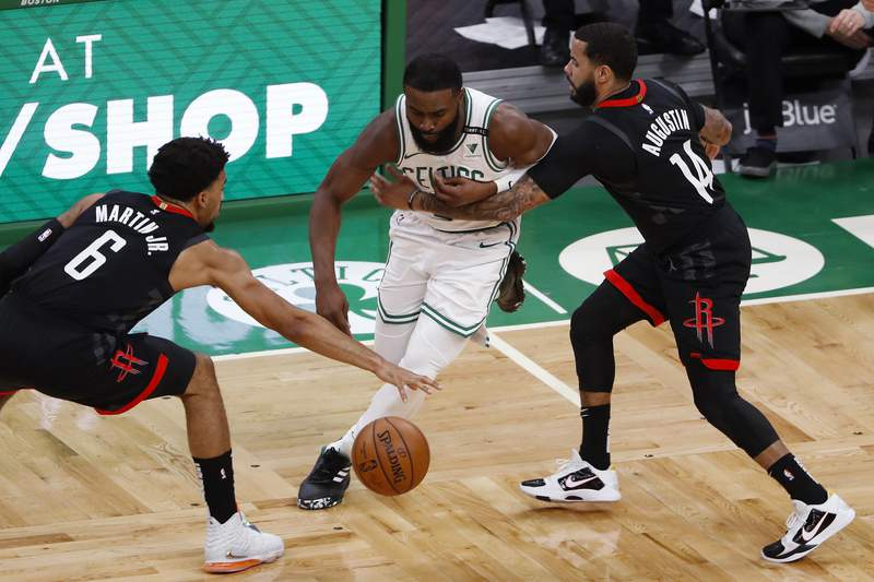 Boston Celtics' Jaylen Brown tries to cut between Houston Rockets' Kenyon Martin Jr. (6) and D.J. Augustin during the second quarter of an NBA basketball game Friday, April 2, 2021, in Boston. (AP Photo/Winslow Townson)