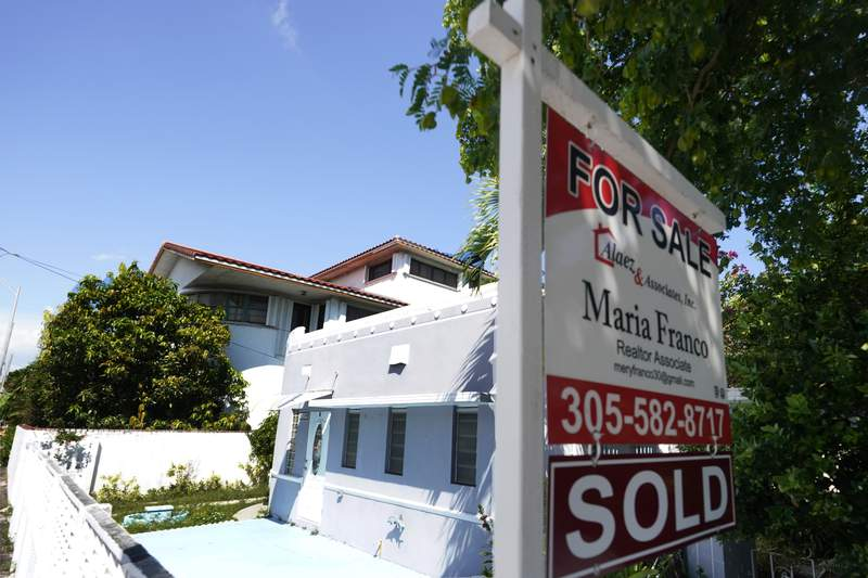 """A home for sale with a """"Sold"""" sign attached is viewed Monday, Oct. 12, 2020, in Miami Beach, Fla.  U.S. long-term mortgage rates remained at record lows this week as the coronavirus pandemic continues to threaten the economy.  (AP Photo/Wilfredo Lee)"""