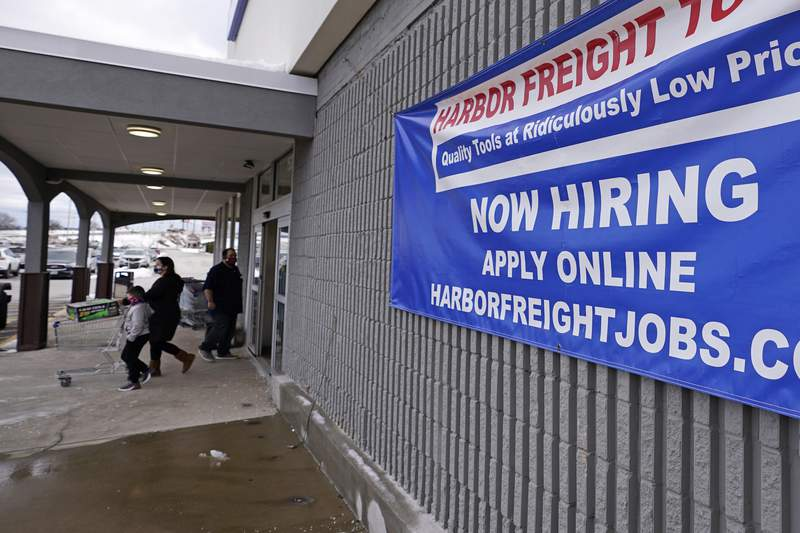 """FILE - In this Dec. 10, 2020 file photo, a """"Now Hiring"""" sign hangs on the front wall of a Harbor Freight Tools store in Manchester, N.H.   U.S. employers cut back sharply on hiring in December, particularly in pandemic-hit industries such as restaurants and hotels, as soaring virus infections and government restrictions weakened the economy that month. The number of available jobs rose slightly and layoffs fell, according to the Labor Departments Tuesday report, known as the Job Openings and Labor Turnover Survey, or JOLTS.  (AP Photo/Charles Krupa, File)"""