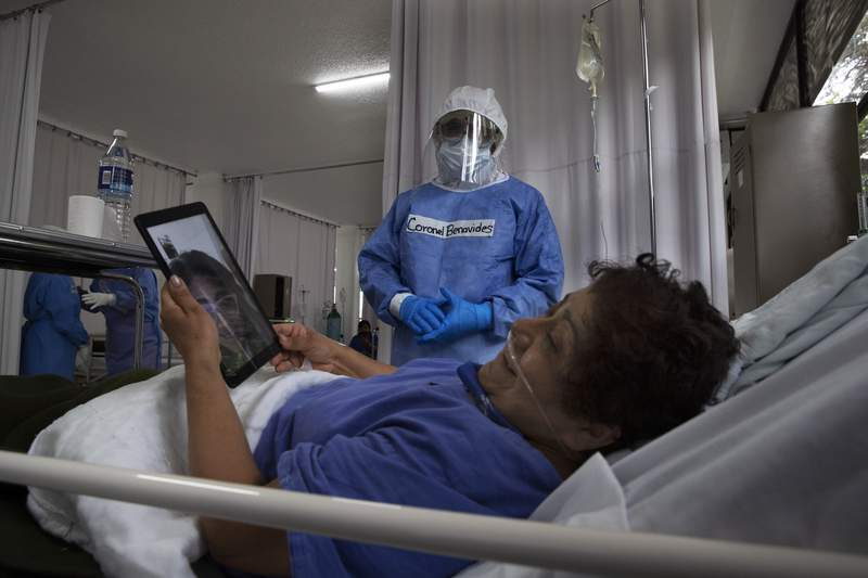 Dressed in protective gear to curb the spread of the new coronavirus, military surgeon, Coronel Oscar Benavides Aguilar talks to a patient who is speaking to her daughter via a tablet, at a military hospital set up to take care of COVID-19 patients in Mexico City, Monday, November 30, 2020. As of last Friday, Mexico reported a record daily increase in the number of coronavirus cases, with Mexico City reporting the biggest portion of the surge in cases. (AP Photo/Marco Ugarte)