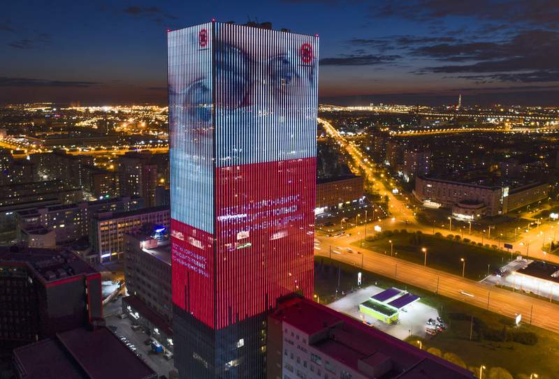An electronic screen, installed on the facade of a business centre, shows an image of a doctor wearing a medical mask and calling to be careful not to become infected with coronavirus in St. Petersburg, Russia, Thursday, April 30, 2020. (AP Photo/Dmitri Lovetsky)