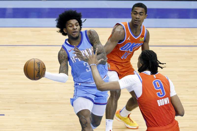 Houston Rockets guard Kevin Porter Jr. (3) passes the ball under pressure from Oklahoma City Thunder guard Theo Maledon (11) and Oklahoma City Thunder center Moses Brown (9) during the second half of an NBA basketball game Sunday, March 21, 2021, in Houston. (AP Photo/Michael Wyke)
