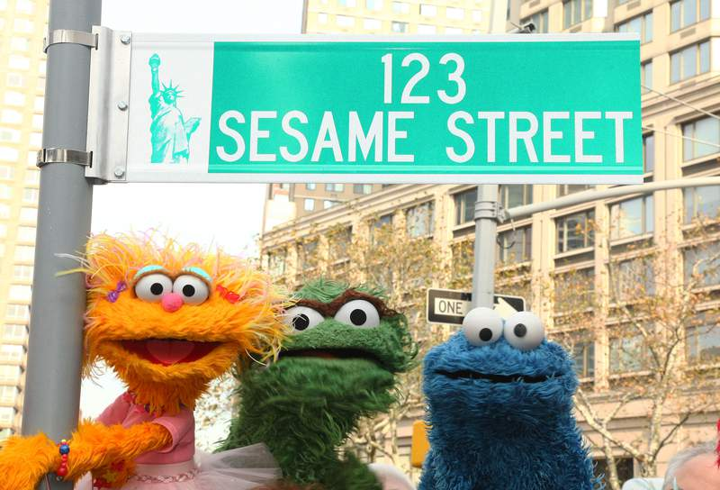 "Sesame Street characters pose under a ""123 Sesame Street"" sign."