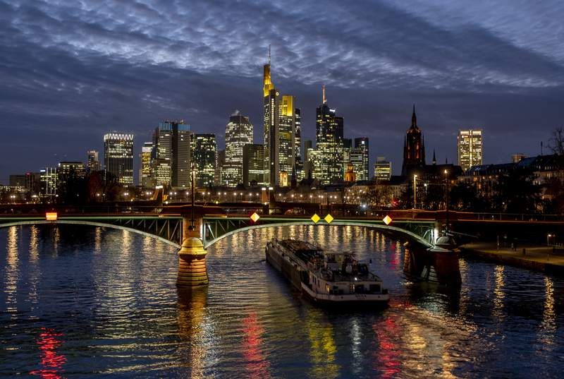 A cargo ship passes under a bridge over the river Main in Frankfurt, Germany, Wednesday, Jan. 13, 2021. (AP Photo/Michael Probst)