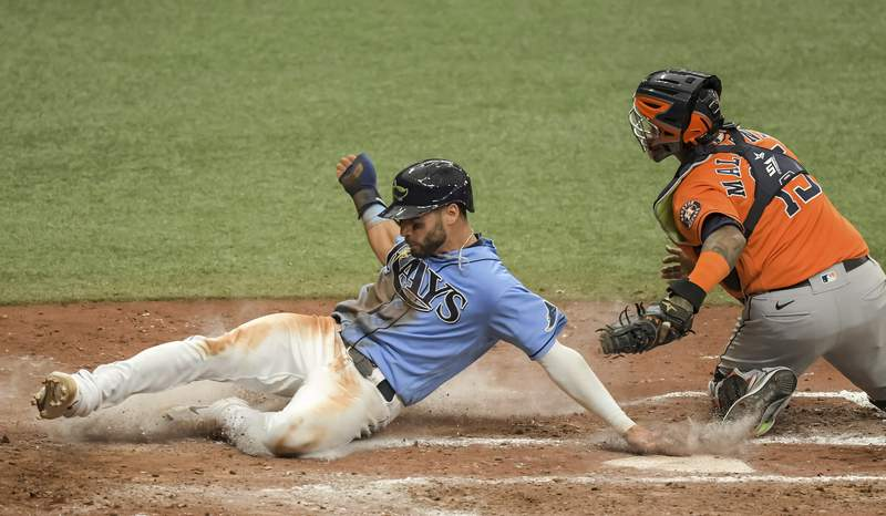 Tampa Bay Rays' Kevin Kiermaier, left, slides past Houston Astros catcher Martin Maldonado, right, to score on Rays' Willy Adames' ground ball to first during the sixth inning of a baseball game Sunday, May 2, 2021, in St. Petersburg, Fla. (AP Photo/Steve Nesius)