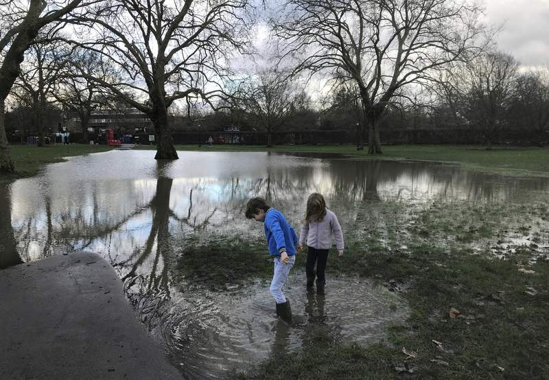 Children play at Primrose Hill Park in London, Jan. 29, 2021, as floodwaters turn a park walkway into a pond. (AP Photo/Sheila Norman-Culp)