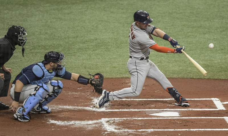 Home plate umpire Chad Fairchild, left, and Tampa Bay Rays catcher Mike Zunino look on as Houston Astros' Alex Bregman hits an RBI-single during the first inning of a baseball game Saturday, May 1, 2021, in St. Petersburg, Fla. (AP Photo/Steve Nesius)