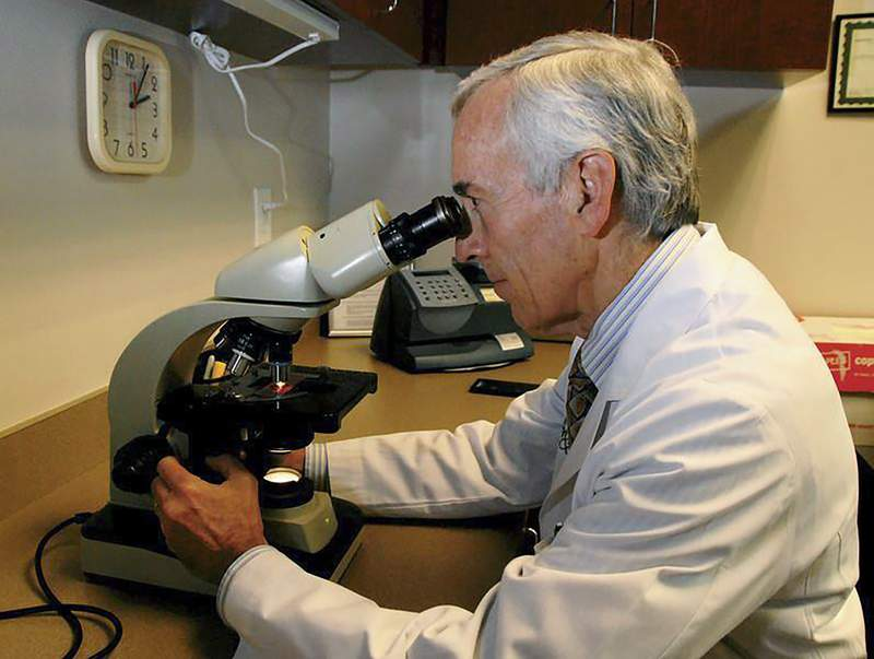 In this undated photo provided by Atlanta Allergy & Asthma, Dr. Stanley Fineman looks through a microscope at Atlanta Allergy & Asthma Center in Atlanta to examine the pollen. When Fineman started 40 years ago as an allergist in Atlanta, he told patients they should start taking their medications and prepare for the onslaught of pollen season around St. Patricks Day. Now he tells them to start around St. Valentines Day. (Robin B. Panethere /Atlanta Allergy & Asthma via AP)