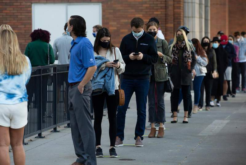 Voters stand in line at the American Airlines Center to cast their ballots on Election Day in Dallas. (Credit: Shelby Tauber for The Texas Tribune)