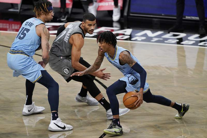 Memphis Grizzlies guard Ja Morant, right, drives past Brooklyn Nets guard Timothe Luwawu-Cabarrot (9) as Grizzlies forward Brandon Clarke (15) sets a screen during the first half of an NBA basketball game Monday, Dec. 28, 2020, in New York. (AP Photo/Kathy Willens)