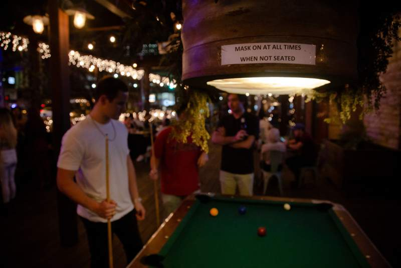 A small sign asks customers at Buford's bar in Downtown Austin to continue following COVID safety guidelines on March 12, 2021, the first weekend after Gov. Greg Abbott removed occupancy limits and lifted restrictions on masks in businesses across Texas.