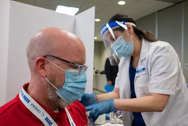 Dave DeJohn, a teacher at Yates High School, gets vaccinated by pharmacist Ilana Druker at Houston Independent School Districts Hattie Mae White Educational Support Center in Houston on Jan. 9, 2020.