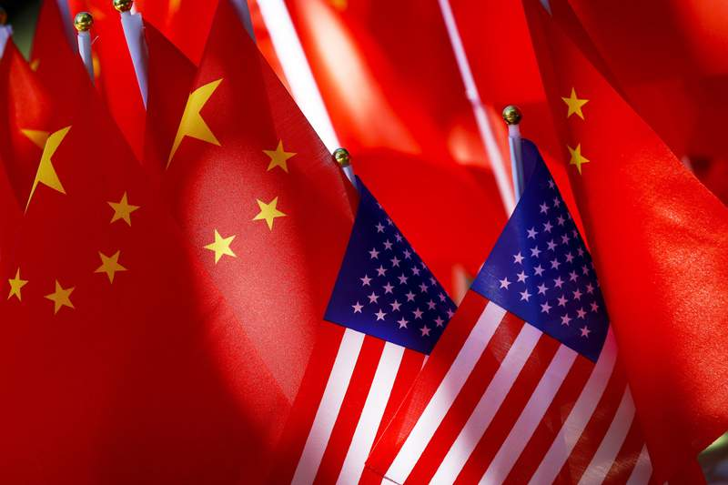 FILE - In this Sept. 16, 2018, file photo, American flags are displayed together with Chinese flags on top of a trishaw in Beijing. China says Friday, Aug. 14, 2020, the United States is trying to demonize and stigmatize bilateral its foreign relations, in a scathing attack on the Trump administration's designation of the Confucius Institute U.S. Center as a foreign mission of the Chinese Communist Party. (AP Photo/Andy Wong, File)