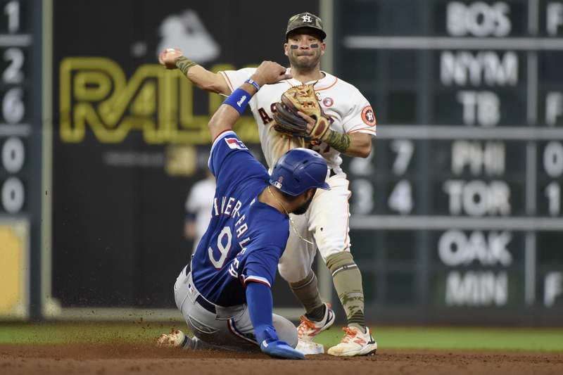 Houston Astros second baseman Jose Altuve, top, attempts a double play over Texas Rangers' Isiah Kiner-Falefa during the eighth inning of a baseball game, Saturday, May 15, 2021, in Houston. Rangers' Andy Ibanez was safe at first. (AP Photo/Eric Christian Smith)