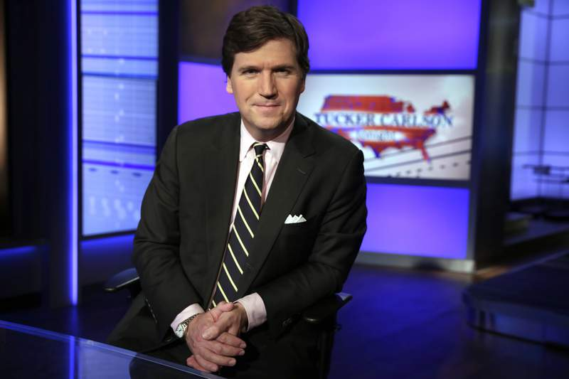 """FILE - In this Thursday, March 2, 2107 file photo, Tucker Carlson, host of """"Tucker Carlson Tonight,"""" poses for a photo in a Fox News Channel studio in New York. The Anti-Defamation League has called for Fox News to fire prime-time opinion host Tucker Carlson because he defended a white-supremacist theory that says whites are being replaced by people of color. In a letter to Fox News CEO Suzanne Scott on Friday, April 9, 2021the head of the ADL, Jonathan Greenblatt, said Carlson's rhetoric was not just a dog whistle to racists  it was a bullhorn.  (AP Photo/Richard Drew, File)"""