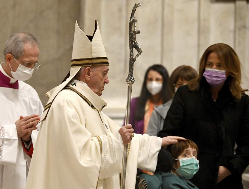 Pope Francis caresses a boy as he arrives to celebrate Mass on Christmas eve, at St. Peter's basilica at the Vatican, Thursday, Dec. 24, 2020. (Vincenzo Pinto/Pool Photo via AP)