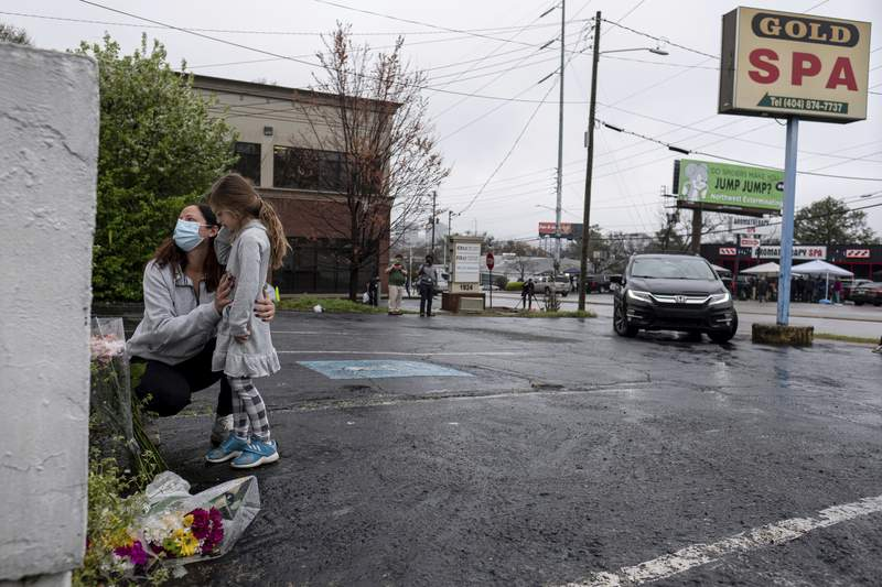 Mallory Rahman and her daughter Zara Rahman, 4, who live nearby, pause after bringing flowers to the Gold Spa massage parlor in Atlanta, Wednesday afternoon, March 17, 2021, the day after eight people were killed at three massage spas in the Atlanta area. Authorities have arrested 21-year-old Robert Aaron Long in the shootings at massage parlors in Atlanta and one in Cherokee County. (AP Photo/Ben Gray)