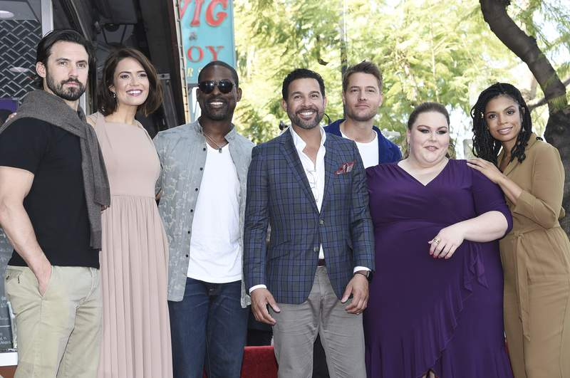 """FILE - In this March 25, 2019, file photo, cast members from """"This Is Us,"""" from left, Milo Ventimiglia, Mandy Moore, Sterling K. Brown, Jon Huertas, Justin Hartley, Chrissy Metz and Susan Kelechi Watson pose for photographers at a ceremony honoring Moore with a star on the Hollywood Walk of Fame in Los Angeles. An optimistic NBC said Thursday, Aug. 27, 2020, it will bring This Is Us and other scripted series back in November despite the TV industry's coronavirus-caused production shutdown that's only beginning to ease. (Photo by Richard Shotwell/Invision/AP, File)"""