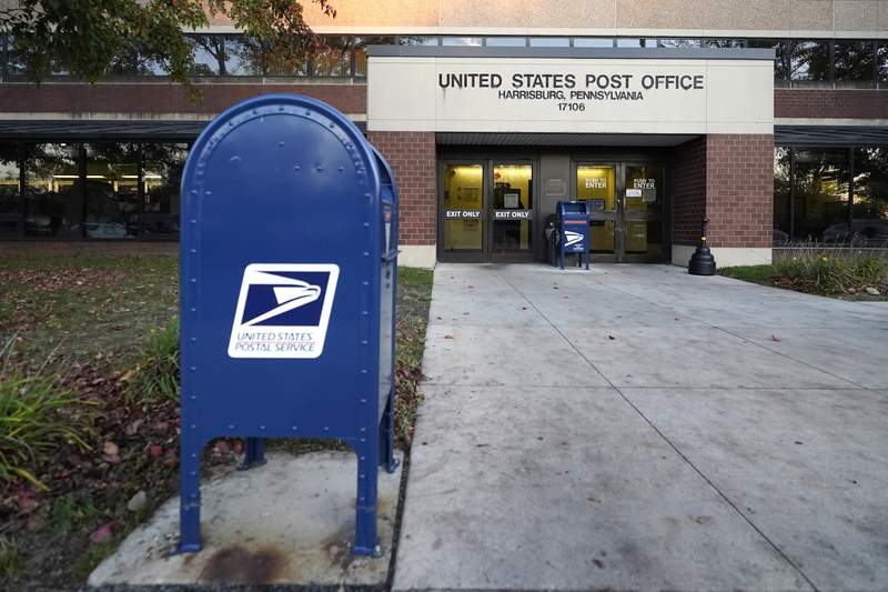 A mailbox sits outside a U.S. Post Office building, Tuesday, Nov. 3, 2020, in the Susquehanna Township section of Harrisburg, Pa. U.S. Postal Service inspectors found just 13 ballots during an Election Day sweep of processing centers ordered by a federal judge, all of them in Pennsylvania. Court documents filed Wednesday, Nov. 4, 2020, say the ballots were then expedited for delivery to local election offices.  (AP Photo/Julio Cortez, File)