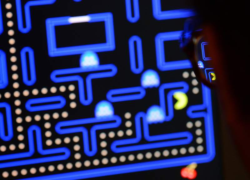 An employee plays the video game Pac-Man (1980) during an exhibition preview featuring 14 video games acquired by The Museum of Modern Art (MoMA)  in New York, March 1, 2013. The MoMA acquired 14 video games entering its collection as part of an ongoing research on interaction design. AFP PHOTO/EMMANUEL DUNAND        (Photo credit should read EMMANUEL DUNAND/AFP via Getty Images)