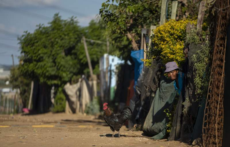 A woman watches as the South African National Defence Forces members patrol the street in Diepsloot informal settlement, north of Johannesburg, South Africa, Thursday, April 16, 2020. South African President Cyril Ramaphosa extended the lockdown by an extra two weeks in a continuing effort to contain the spread of COVID-19 coronavirus. (AP Photo/Themba Hadebe)