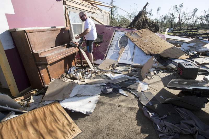 David Maynard sifts through the rubble searching for his wallet, Thursday, April 23, 2020 in Onalaska, Texas, after a tornado destroyed his home the night before. Maynard was inside his home when a tornado devastated the area. (Brett Coomer/Houston Chronicle via AP)