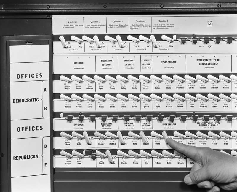 """The original caption on this undated photo says, """"After you have completed casting your ballot, move the large curtain handle to the left. This will record your vote, wipe off the 'X' marks and return all the voting levers to an upright position, before opening the curtain."""""""