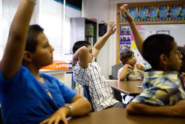 Science students at Bayless Elementary in Lubbock raise their hands to answer a question posed during a water conservation presentation.      Jerod Foster for the Texas Tribune