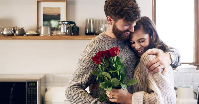 Shot of a young man surprising his wife with a bunch of roses at home