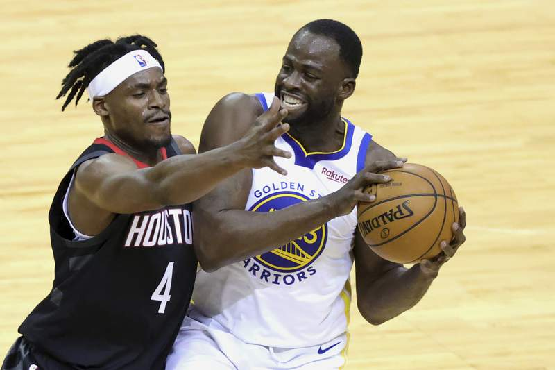 Golden State Warriors' Draymond Green keeps the ball from Houston Rockets' Danuel House Jr. during the first quarter of an NBA basketball game Wednesday, March 17, 2021, in Houston. (Carmen Mandato/Pool Photo via AP)