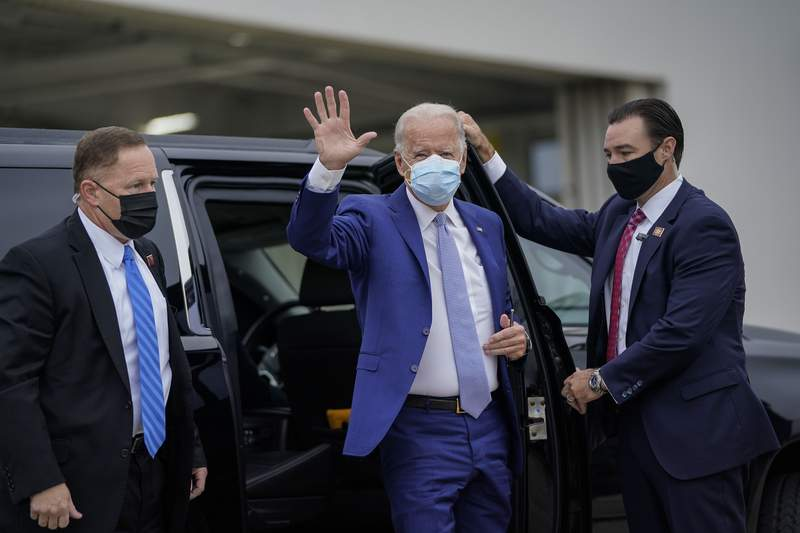 Democratic presidential nominee Joe Biden waves as he arrives to board his campaign plane at New Castle Airport on Oct. 27, 2020, in New Castle, Delaware. Biden is campaigning in Georgia on Tuesday, with scheduled stops in Atlanta and Warm Springs.