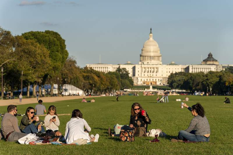 FILE - In this Oct. 8, 2020, file photo with the Capitol in the background, two women toast in the air from afar while enjoying a warm fall afternoon as the sun begins to set on the National Mall in Washington. Officials in the nation's capital are questioning the results of the 2020 census, which show a large boost in population but not as high as they had expected. (AP Photo/Jacquelyn Martin, File)