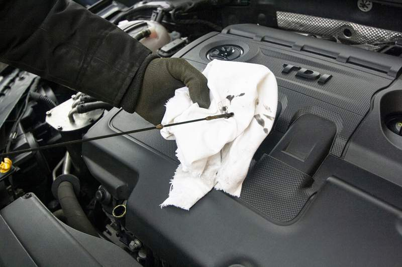 A person shows how to change the oil in a vehicle.
