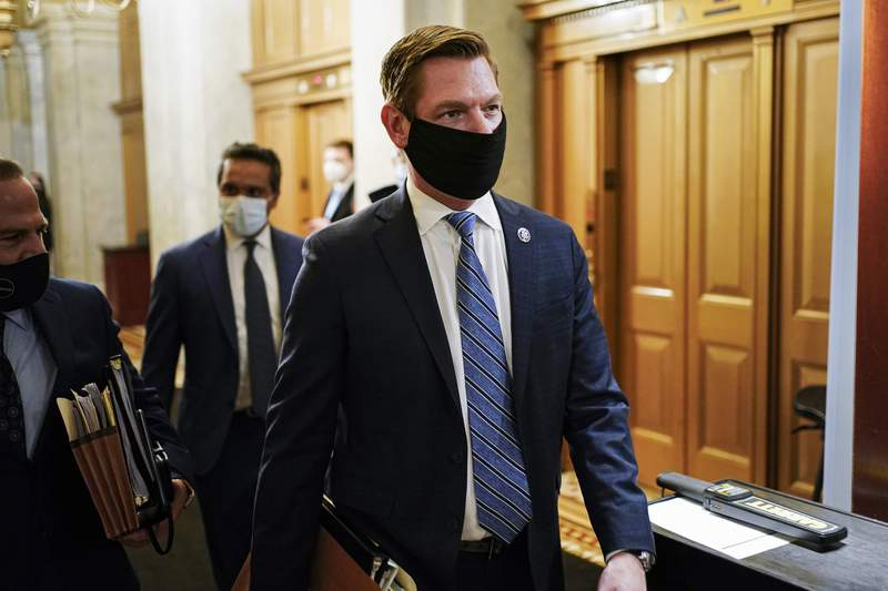 FILE - In this Feb. 10, 2021, file photo, Rep. Eric Swalwell, D-Calif., walks at the Capitol, in Washington. The House has rejected an attempt to boot a Democrat from the House intelligence committee. Democrats scuttled a Republican effort to remove Swalwell from the intelligence panel. The resolution against Swalwell cited reporting that he had contact more than six years ago with a suspected Chinese spy who targeted politicians in California. (Joshua Roberts/Pool via AP, File)