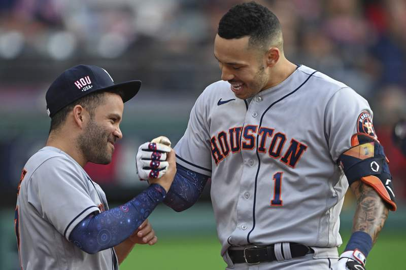 Houston Astros' Carlos Correa, right, is congratulated by Jose Altuve after hitting a solo home run off Cleveland Indians starting pitcher Eli Morgan during the fourth inning of a baseball game Saturday, July 3, 2021, in Cleveland. (AP Photo/David Dermer)