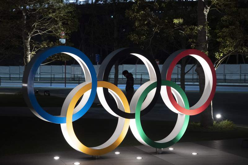 FILE - In this March 24, 2020, file photo, a man is seen through the Olympic rings installed near the National Stadium in Tokyo. Athletes at the Tokyo Olympics who come down with minor symptoms of COVID-19 could be isolated in a hotel lined up by local organizers of the games. Japans Kyodo news agency cited unnamed officials with knowledge of the plan. The Japanese news agency on Sunday, April 11, 2021, said organizers are working to secure 300 rooms in a hotel near the Athletes Village. (AP Photo/Jae C. Hong, File)