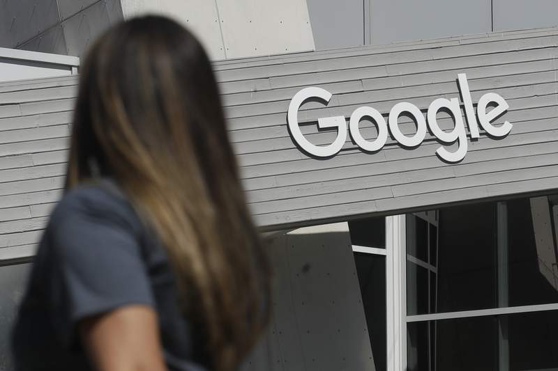 FILE - In this Sept. 24, 2019, file photo a woman walks below a Google sign on the company's campus in Mountain View, Calif. A group of Google engineers announced Monday, Jan. 4, 2021, they have formed a union, creating a rare foothold for the labor movement in the tech industry. (AP Photo/Jeff Chiu, File)