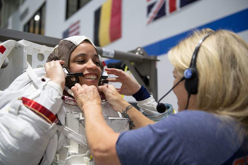 2017 NASA astronaut candidate Jessica Watkins is helped into a spacesuit prior to underwater spacewalk training at NASA Johnson Space Center's Neutral Buoyancy Laboratory in Houston.