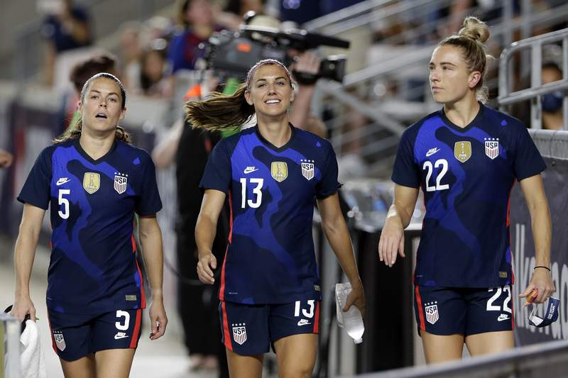 FILE - In this June 13, 2021, file photo, United States defender Kelley O'Hara (5), forward Alex Morgan (13) and midfielder Kristie Mewis (22) walk onto the field before their soccer game against Jamaica in Houston. Morgan says the U.S. women's national team needs to make sure players aren't losing any compensation they currently receive under U.S. Soccer's identical contract proposals for both the men's and women's teams. But the team is hopeful for a new collective bargaining agreement that will address players' concerns about equitable pay, she said. (AP Photo/Michael Wyke, File)
