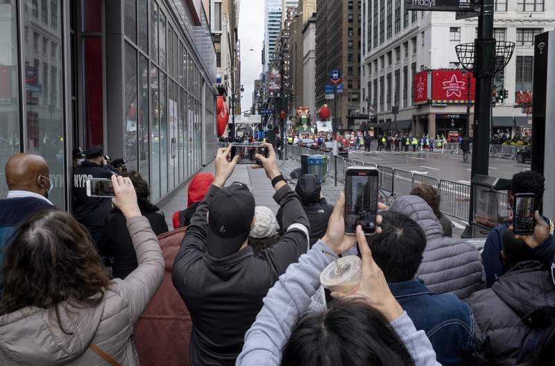 People attempt to take photos as the last floats that are part of the modified Macy's Thanksgiving Day Parade move away in New York, Thursday, Nov. 26, 2020. Due to the pandemic, crowds of onlookers were not allowed to attend the annual parade. (AP Photo/Craig Ruttle)