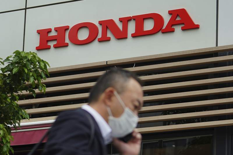A man wearing a protective mask to help curb the spread of the coronavirus walks past the logo of Honda Motor Company in Tokyo on May 13, 2021. Honda returned to profitability in April-June, recording a 222.5 billion yen ($2 billion) profit, as better sales and costs cuts added to the Japanese automakers bottom line. (AP Photo/Eugene Hoshiko)
